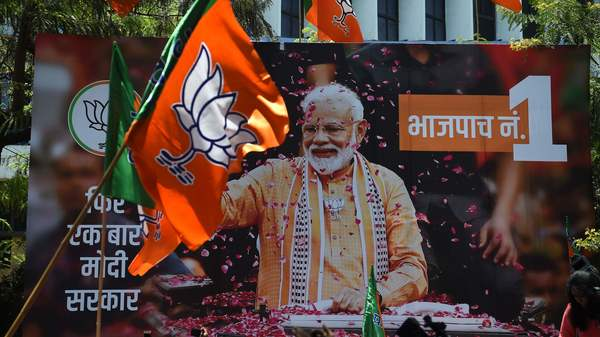 A billboard with an image of Indian Prime Minister Narendra Modi is surrounded by Bharatiya Janata Party (BJP) flags as supporters gather to celebrate the election results outside the BJP headquarters in Mumbai on May 23, 2019. - Indian Prime Minister Narendra Modi looked on course May 23 for a major victory in the world's biggest election, with early trends suggesting his Hindu nationalist party will win a bigger majority even than 2014. (Photo by PUNIT PARANJPE / AFP)